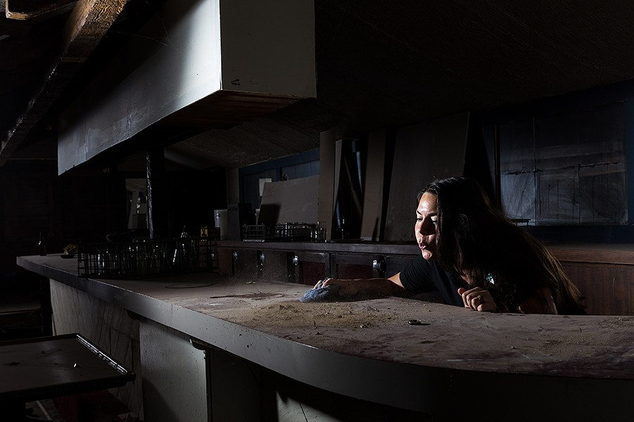 Bartender Lexi Alfonso blows dust off the bar in the basement of O'Doherty's Irish Grille in downtown Spokane. Now relegated to a dimly lit storage area, the bar was remodeled in the 1980s when the room was used as a comedy club. - STEPHEN SCHLANGE
