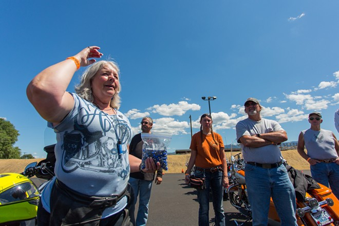 Becky Rohwer, left, ride leader, demonstrates to the bikers the hand signals that everyone will use. - MATT WEIGAND