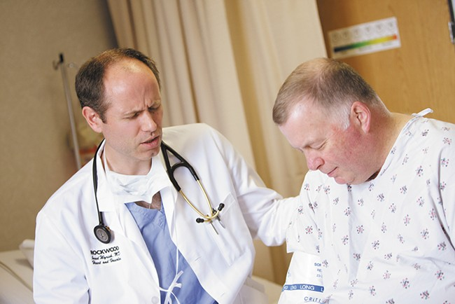 Before a procedure, Dr. Jared Wyrick prays with his patient Greg Boyle at Deaconess Medical Center. - YOUNG KWAK