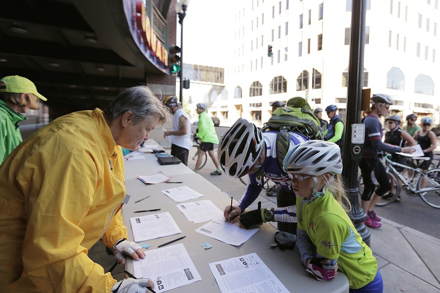 Brian Constock, center, and his 9 year old daughter Kennedy, right, register for the REI 21 Mile River Loop route as volunteer Nancy Tressler looks on. - YOUNG KWAK
