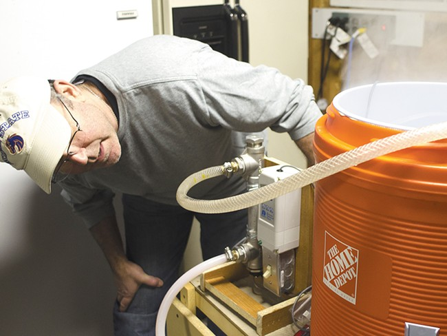Brian Kennedy inspects his homebrewing system. - JACOB JONES