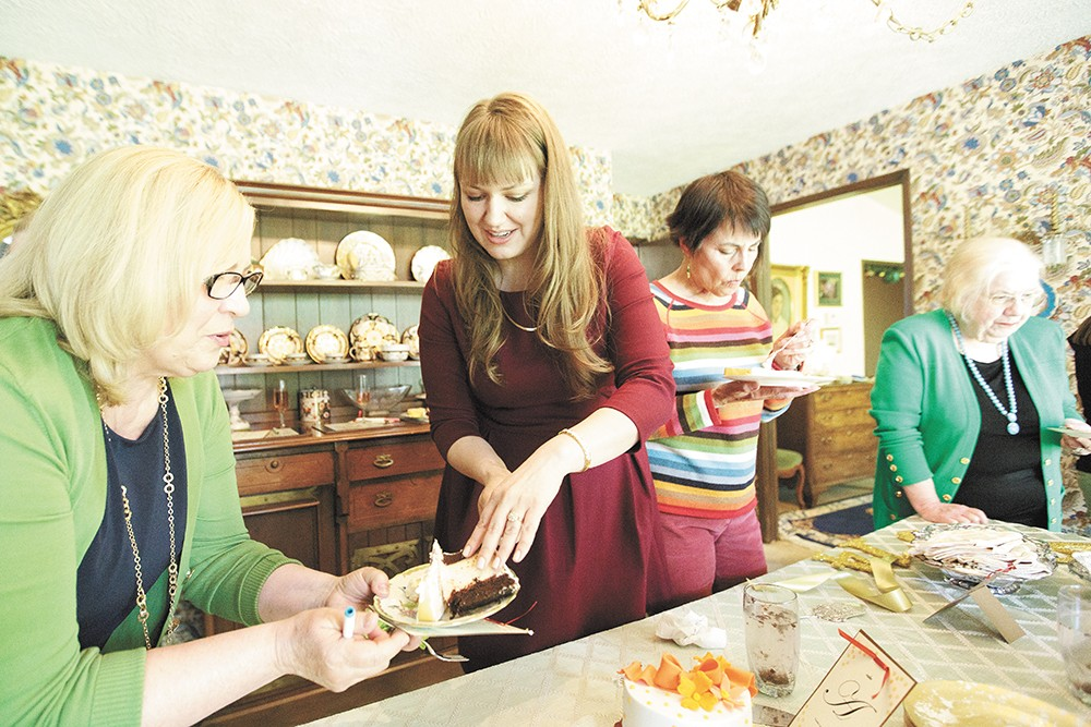 Bride-to-be Charlotte Boutz, center, serves Happy Cake Co.'s Tuxedo Cake with raspberry filling to Karen Fitzpatrick during a bridal shower. - YOUNG KWAK