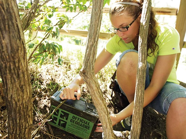 Brittnee Garrett, 21, uncovers a geocache in Manito Park and logs her find online and in the cache's log book. - YOUNG KWAK