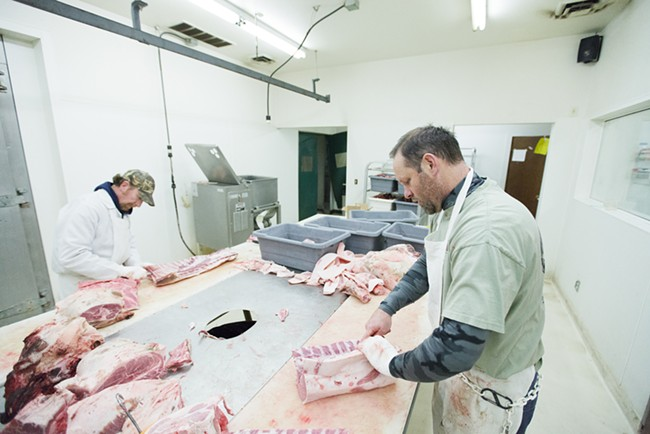 Tim Branen, right, and Mike Cobetto trim pork. - YOUNG KWAK