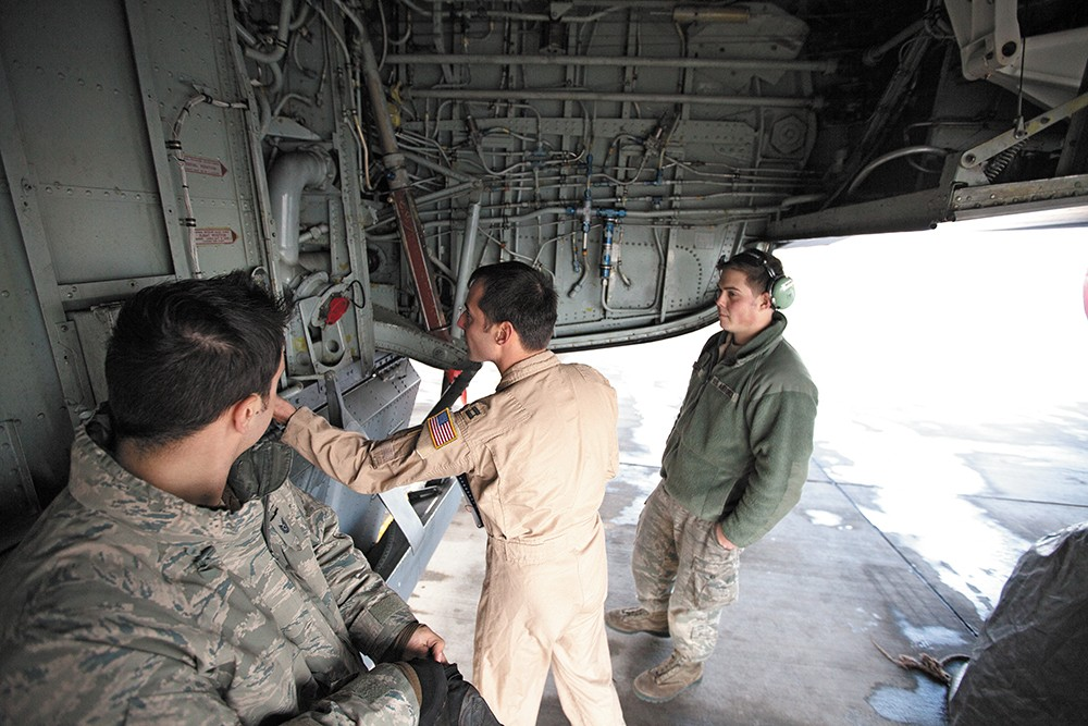 Captain Mike Dobbs, right, checks the wheel well of a KC-135 at Manas, as Senior Airman Nick Stevens looks on. - YOUNG KWAK