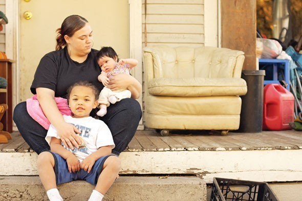 Carol's daughter, Carrie Collette, sits with her son, Dion, and daughter Eillie in front of their east Spokane home. It will be bulldozed next year to make way for the North-South Freeway, and Collette fears she won't find a safe place for her family because of her own felony record. - YOUNG KWAK