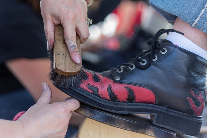 Carolyn Fritz, of Phoenix, has her boot polished by Angie Spencer of Black Sheep, Harley Davidsons For Christ, at Lone Wolf Harley Davidson. - MATT WEIGAND