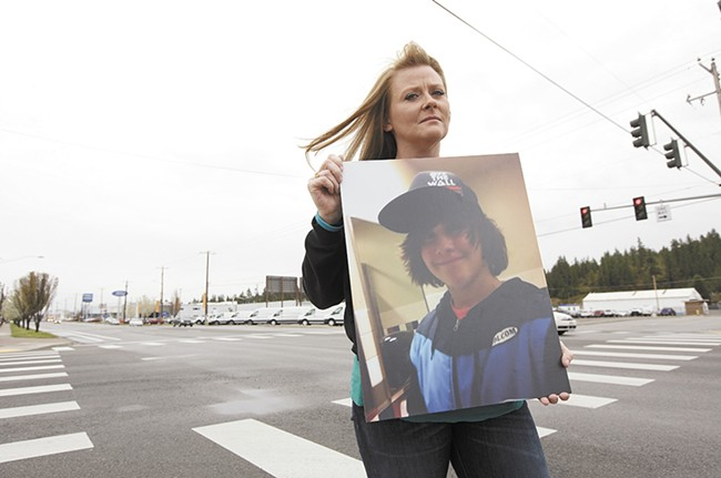 Carrie Thomson holding a photograph of her son Ryan Holyk at the intersection where Ryan sustained fatal injuries. - YOUNG KWAK