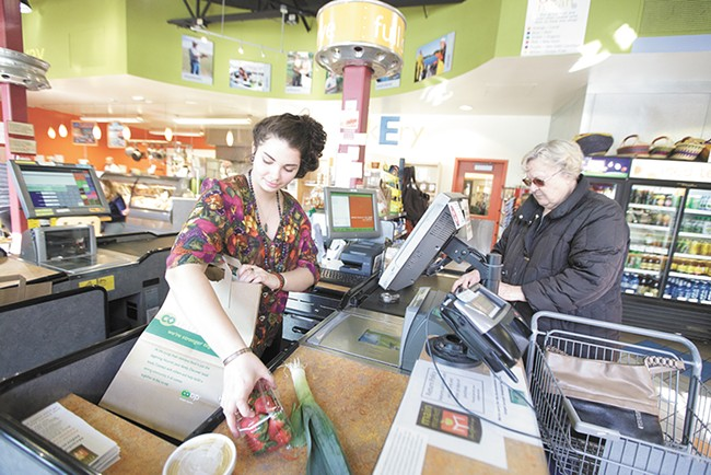 Cashier Syd Silva bags groceries for Halina Slobodow at Main Market Co-op. - YOUNG KWAK