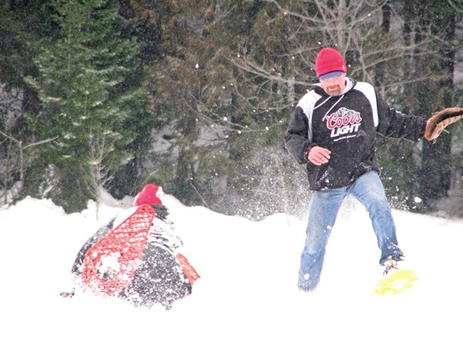 Catching a softball is complicated by snowshoes. - PECKY COX