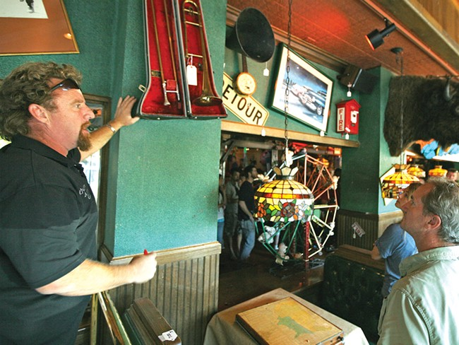 Chet Culp of Owen's Auction helps sell one of 150 pieces of decor on the walls at now-shuttered Cyrus O'Leary's. - YOUNG KWAK
