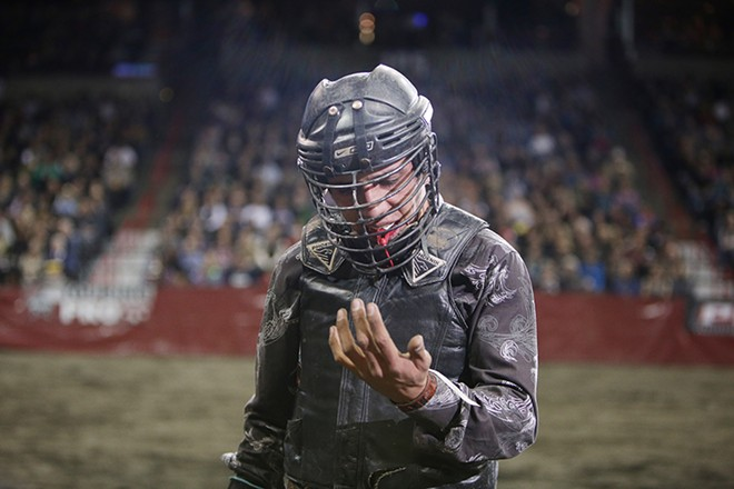 Chon Miranda, of Ruidoso Downs, N.M., looks at his hand after riding K46 Super Fly, not pictured, during the Championship Round, on Saturday. He rode 4.87 seconds before falling off the bull. - YOUNG KWAK