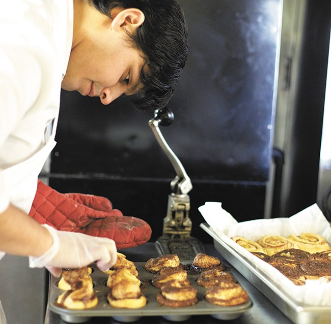 Clay Cerna, general manager of Sweetbox Delivery, works on his cinnamon rolls at Kitchen Spokane. - YOUNG KWAK
