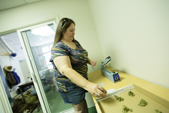 Co-Owner Johanna Tuttle bags one gram New York City Diesel marijuana bags. - YOUNG KWAK