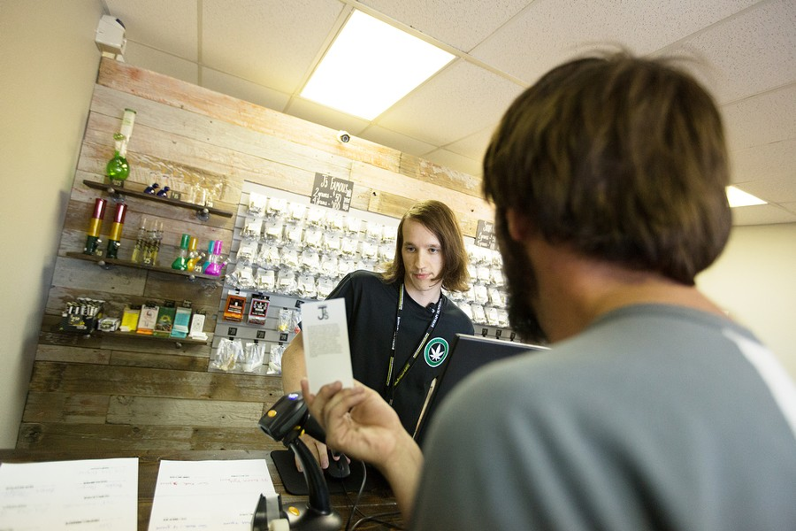 Spokane Green Leaf employee Chad Walsh, left, goes over a menu with customer Alex Rehberg. - YOUNG KWAK