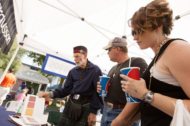 Dan Ferguson, left, shows a book of tartans to Dan, center, and Laci Murdock at the Clan Fergusson tent. Dan Murdock was looking for his family's tartan. - YOUNG KWAK