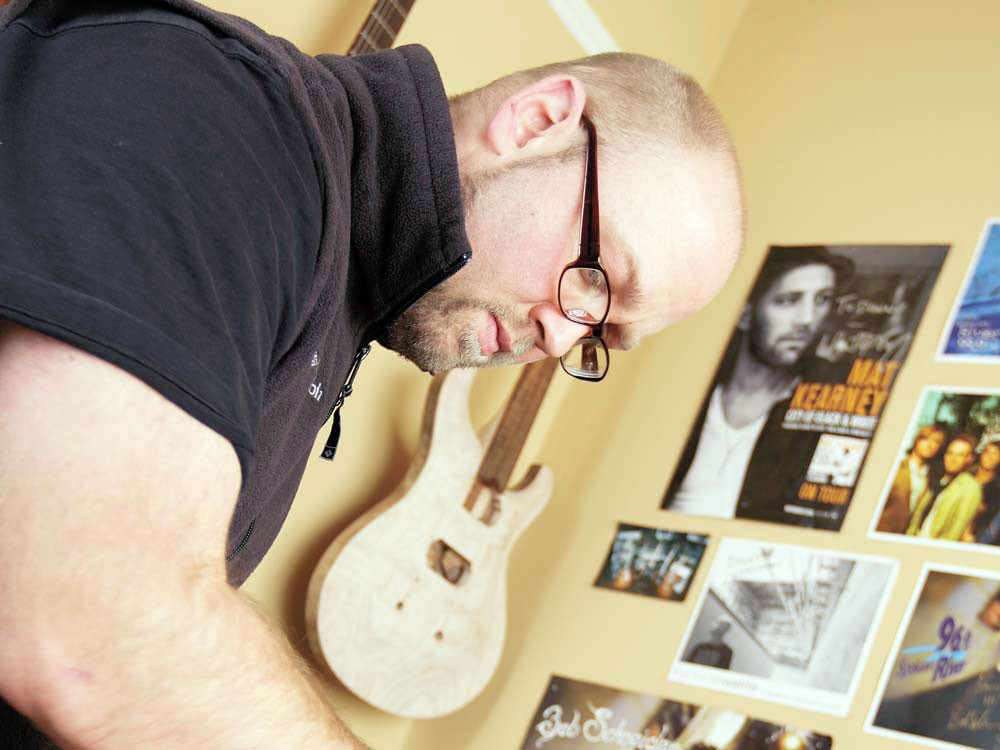 Danny Songhurst carving the neck of a guitar. - YOUNG KWAK