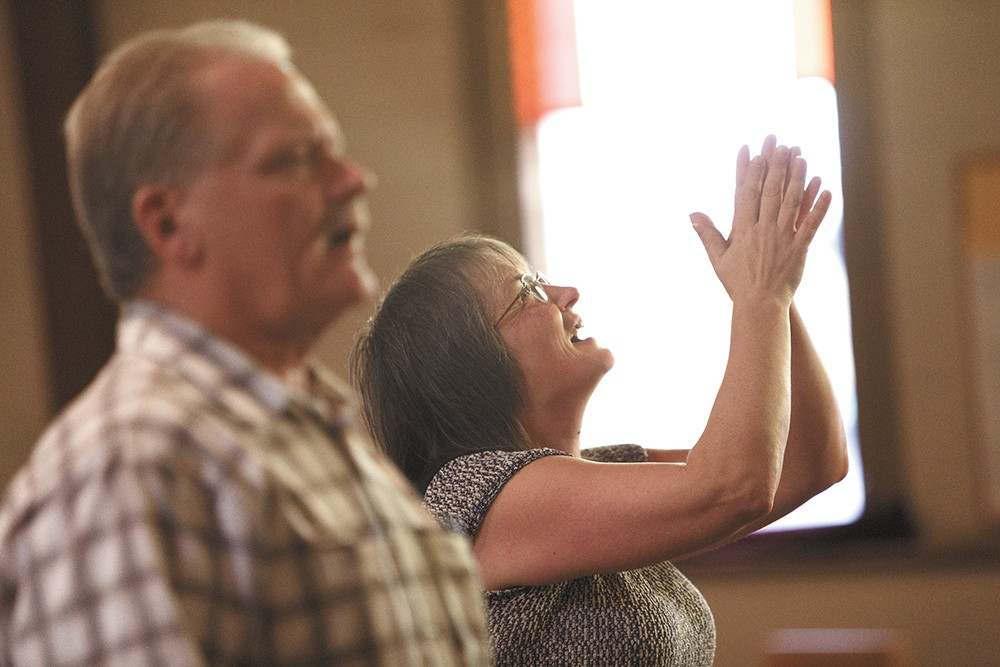 Darla Marlow, right, worships during services at First Covenant Church. - YOUNG KWAK