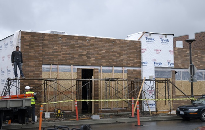 Despite the rain, workers make progress on the new home for Veraci Pizza. - LISA WAANANEN