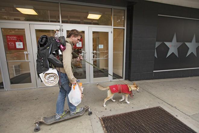 Dillon Green skates behind his mixed breed dog, Katara, past Macy's in downtown Spokane on Sept. 26. - YOUNG KWAK