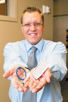 Dr. Jason Reuter displays various contraceptives available at Spokane OBGYN. - STEPHEN SCHLANGE