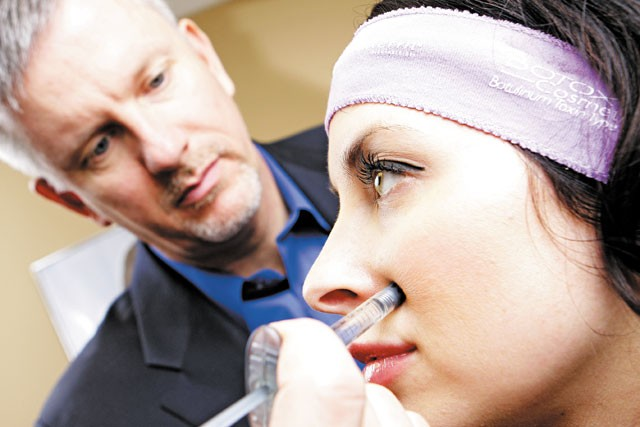 Dr. John Lundeby of Reflections  Med Spa demonstrates a botox procedure on Courtney Thomas. - YOUNG KWAK