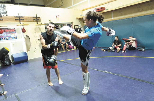Elizabeth Phillips, right, kicks while sparring with Ron Nance at Sik-Jitsu. - YOUNG KWAK