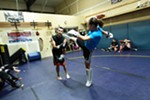 Elizabeth Phillips, right, kicks while sparring with Ron Nance.