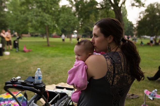 Emerson-Garfield Neighborhood Council Member Eline Helm with her 6-month-old daughter Linnea listening to the Sara Brown Band. - YOUNG KWAK