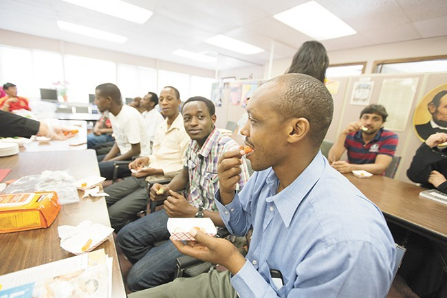 Rwandan refugee Emmanuel Rucyahana, right, tries a carrot during a nutrition workshop at World Relief Spokane last week. Funding for workshops like this one had been redirected to address immigration at the southern border but has now been restored. - YOUNG KWAK PHOTO