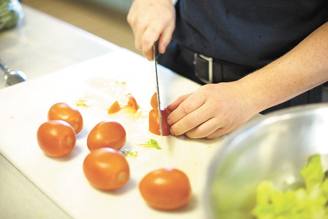 Firefighter Jason Keen slices a tomato for a salad.| - YOUNG KWAK