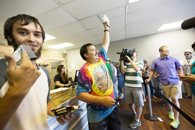 First customer Mike Boyer, center, and Alex Rehberg, left, hold their two-grams packages of Farmer J's Sour Kush at Spokane Green Leaf. - YOUNG KWAK