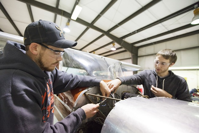 First year students Josh Newberg, left, and Nick Bell install solenoids into a Cessna 150. - YOUNG KWAK