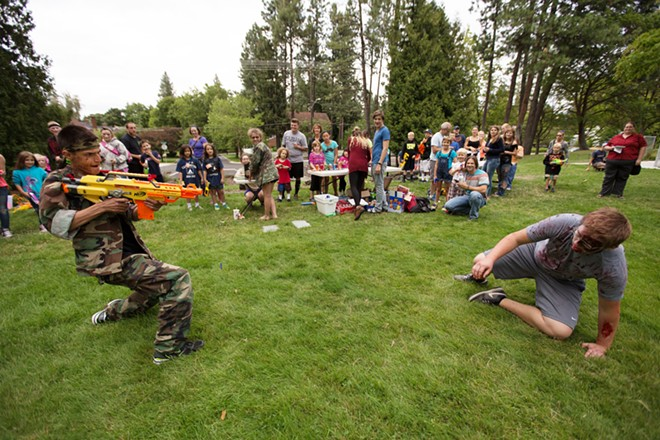 Founder Adin Haines, left, shoots zombie Dillon Kummer while giving a welcome speech to participants. - YOUNG KWAK
