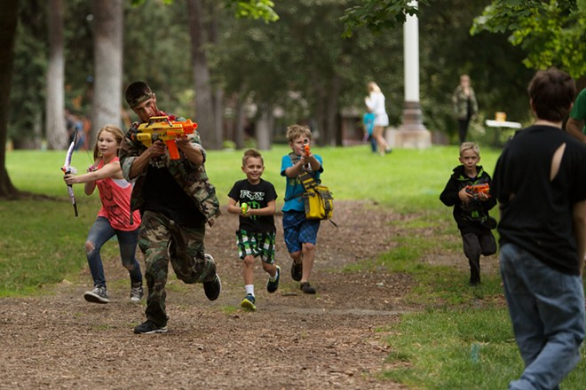 Founder Adin Haines, second from the left, shoots at zombies while leading race participants. - YOUNG KWAK