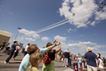 George Laplace, in the foregrond, points to passing U.S. Air Force Thunderbirds Air Demonstration Squadron F-16s as his 8-year-old daughter Celeste watches.