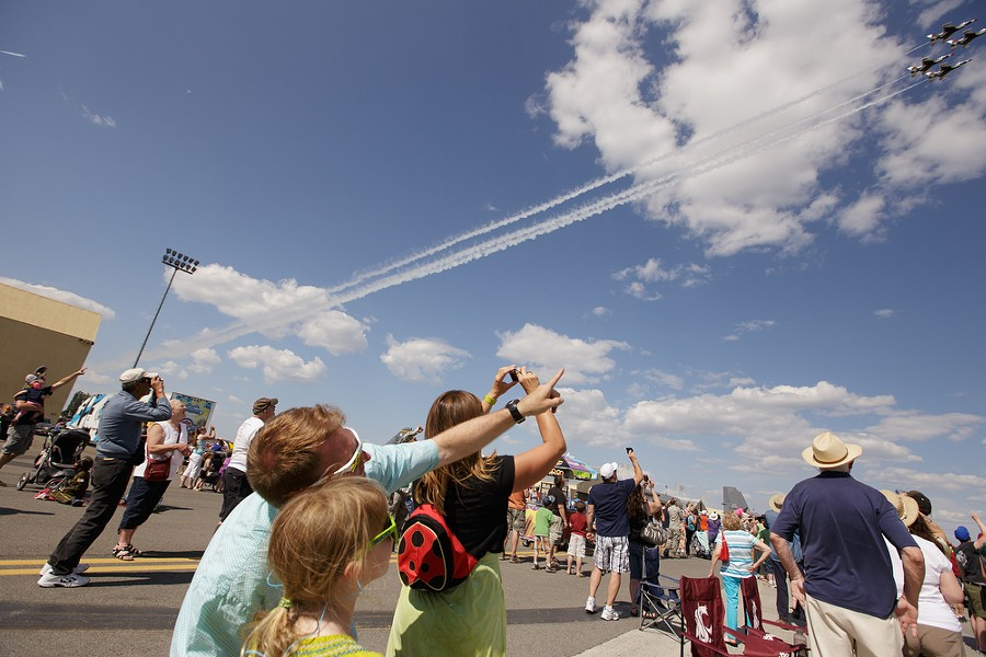 George Laplace, in the foregrond, points to passing U.S. Air Force Thunderbirds Air Demonstration Squadron F-16s as his 8-year-old daughter Celeste watches. - YOUNG KWAK
