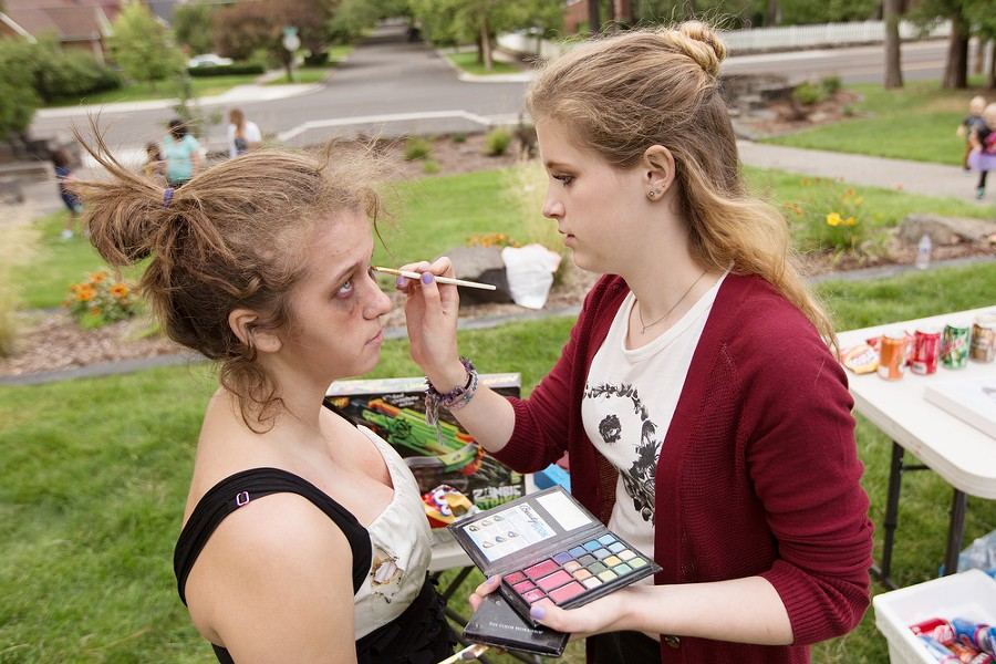 Volunteer Heidi Lockhoff, right, puts makeup on volunteer Sam Gill before the Zombie Run. - YOUNG KWAK