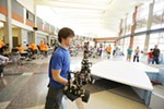 Horizon Middle School 8th grader Michael Sampson prepares to test his robot before MINDS-i competition.