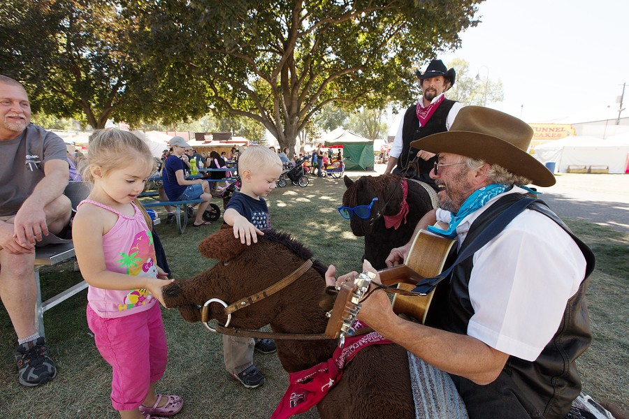 In their horse costumes Buddy and Fame, Earl Baze (Simon), right, and Jason Rariden (Curly), second from the right, entertain 3 1/2 year olds Isla Stephens, left, and Harlan Foster. - YOUNG KWAK