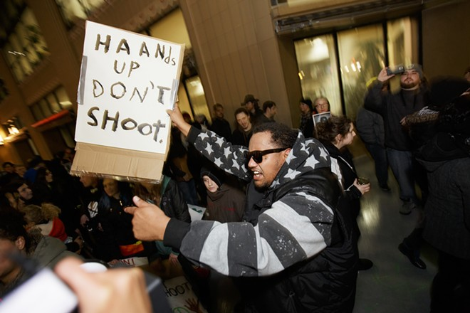 Israel Jones, center, holds a sign in front of city hall. - YOUNG KWAK