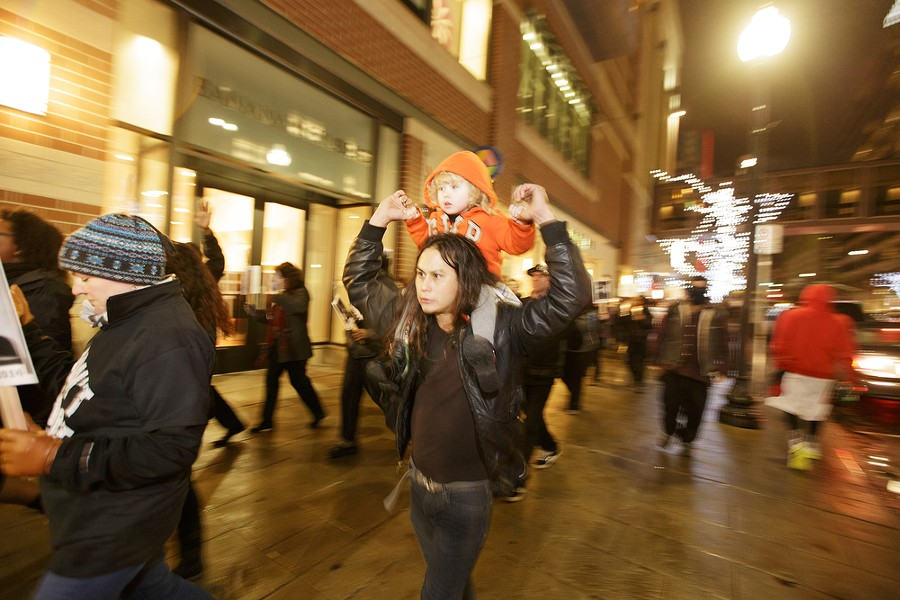 Jacob Johns, center, carries his 2-year-old daughter Lily while walking down W. Main Ave. - YOUNG KWAK