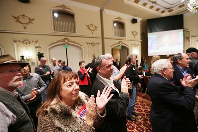 Jaime Thiel, left, and her husband Jim, center, applaud as election results are posted - YOUNG KWAK