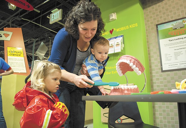 Jami Cary and her kids Rose and Justin work on toothbrushing at Mobius. - SARAH WURTZ