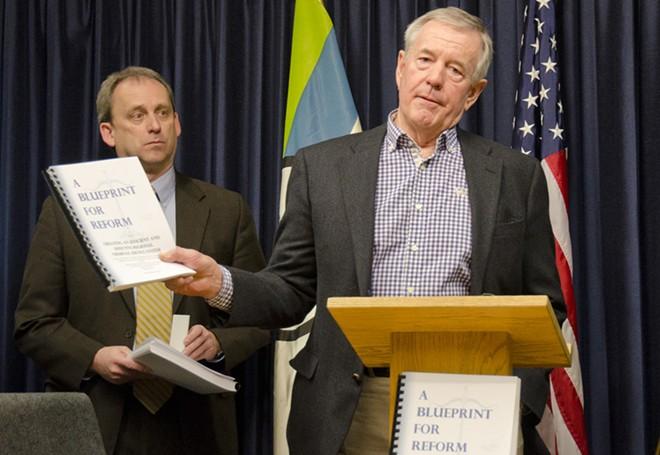 Jim McDevitt holds up the final report from the Spokane Regional Criminal Justice Commission. - JACOB JONES