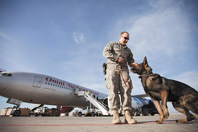 K9 Handler Senior Airman Zach Villano and his dog Spikey prepare to do a security sweep of a plane. - YOUNG KWAK