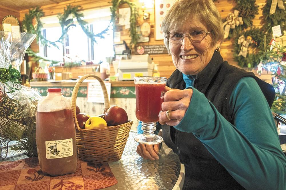 Karen Hansen with a glass of her family's cherry apple cider at Hansen's Green Bluff Orchard. - SARAH WURTZ