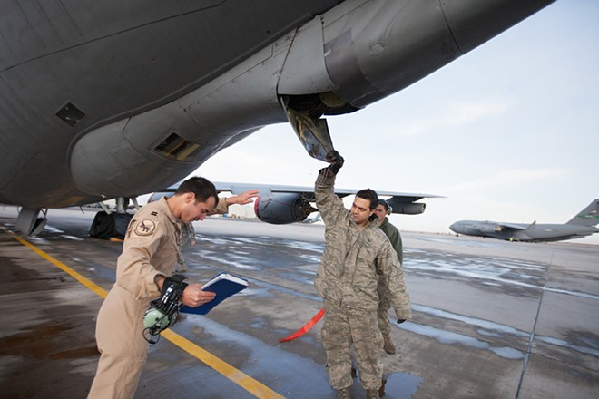 376th Expeditionary Operations Group Captain Mike Dobbs, center, and 376th Expeditionary Aircraft Maintenance Squadron Senior Airman Nick Stevens, right, check a hatch on a KC-135 as and Airman First Class Joshua Jones looks on. - YOUNG KWAK