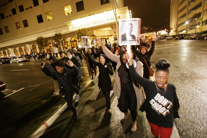 Lanae Dedmond, right, and others chant while walking down S. Post Ave. - YOUNG KWAK