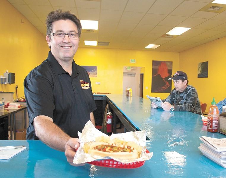 Lavadog owner Eric Burkholder with a Hawaiian take on a chili dog. - ASHLEY TOMLINSON